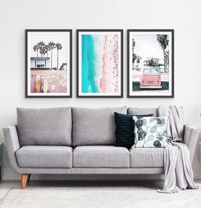 Three photo prints of California beach house, surfing boards, a coast and a surfing miniwan in white frames