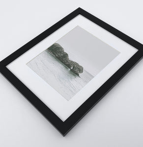 A framed photo print with a rock in the ocean