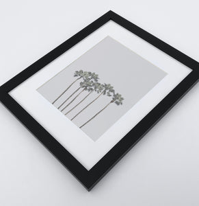 A framed photo print with palms