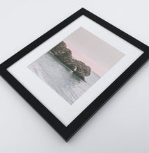 Load image into Gallery viewer, A big dark gray rock popping out of the ocean in a light ping sunrise on a photo print in a black frame