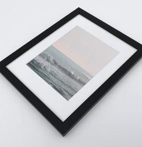 Big fluffy ocean waves in a light pink sunrise sky photo print in a black frame
