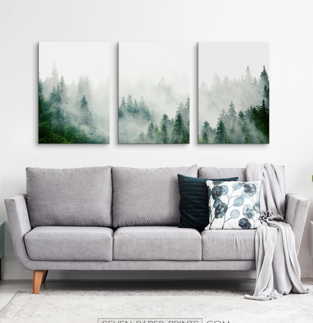 Three misty forest photo prints hanging on wall above the big living room sofa