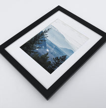 Load image into Gallery viewer, A photo print of blue mountains and a forest in black frame