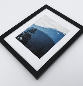 A photo print of blue mountains and a forest in black frame