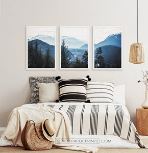 Three photo prints of blue mountains and a forest above the bed