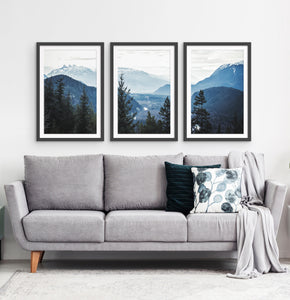 Three photo prints of blue mountains and a forest above the sofa