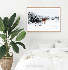 Horse in a snowy landscape wall art in a wooden frame in the interior