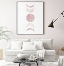 Load image into Gallery viewer, Black-Framed Moon Phases Watercolor Print in Bage and Brown on a living room wall