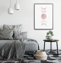 Load image into Gallery viewer, Black-Framed Moon Phases Watercolor Print in Bage and Brown on a bedroom wall