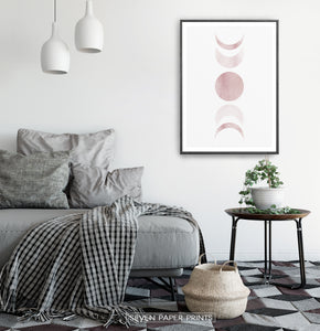Black-Framed Moon Phases Watercolor Print in Bage and Brown on a bedroom wall
