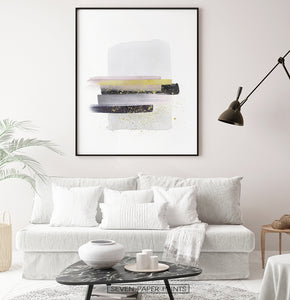 A framed poster with gray, yellow, and black horizontal smears on white background - in the living room