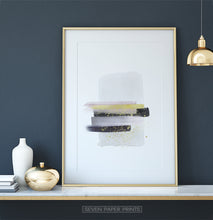 Load image into Gallery viewer, A golden-framed poster with gray, yellow, and black horizontal smears on white background - on a shelf