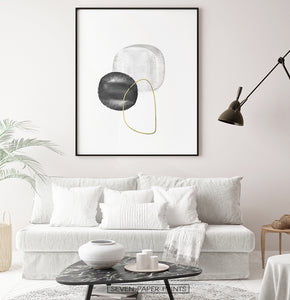 A black-framed wall art with black, silver and golden forms in a living room