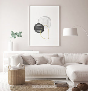A white-framed wall art with black, silver and golden forms in a living room