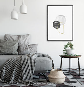 A black-framed wall art with black, silver and golden forms in a bedroom