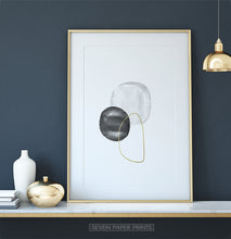 Load image into Gallery viewer, A golden-framed wall art with black, silver and golden forms on a shelf