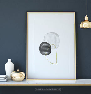 A golden-framed wall art with black, silver and golden forms on a shelf