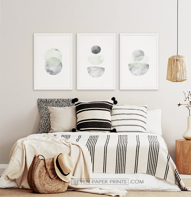 Three framed prints with abstract moon-like art in green, gray and black tones on white background