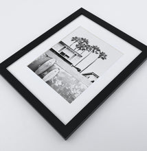 Load image into Gallery viewer, A boat coastal house with surfing boards in a black frame