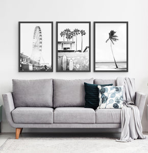 Photos of a ferris wheel, a boat coastal house with surfing boards and a palm on a beach, in frames hanging above the living room sofa