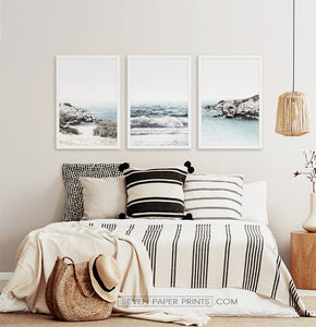 Three white shore of the ocean photos in frames above the bed