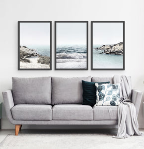 Three white shore of the ocean photos in frames above the sofa