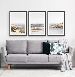 Three photo prints of sandy ocean shore in natural colors in black frames
