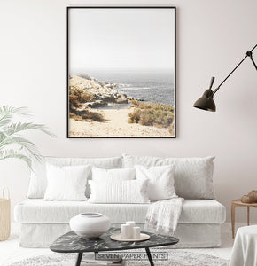 Beige gray rocky beach wall art above the white sofa in living room
