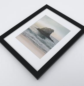 A framed print with rock in a stormy ocean