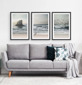 Three framed prints with a stormy ocean landscape
