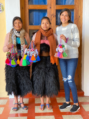 The owner of Xula Handmade, Jessica with two women artisans holding embroidered skull tassels