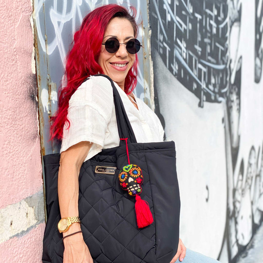 Hand embroidered red sugar skull tassel on a woman's black tote