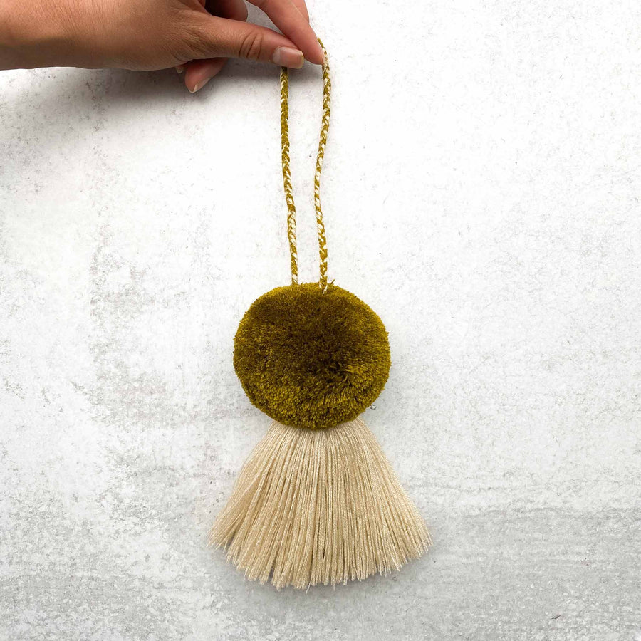 Holding Handmade-Large-Pom-Tassel-for-Handbag in Olive Green Pom with Beige Tassel