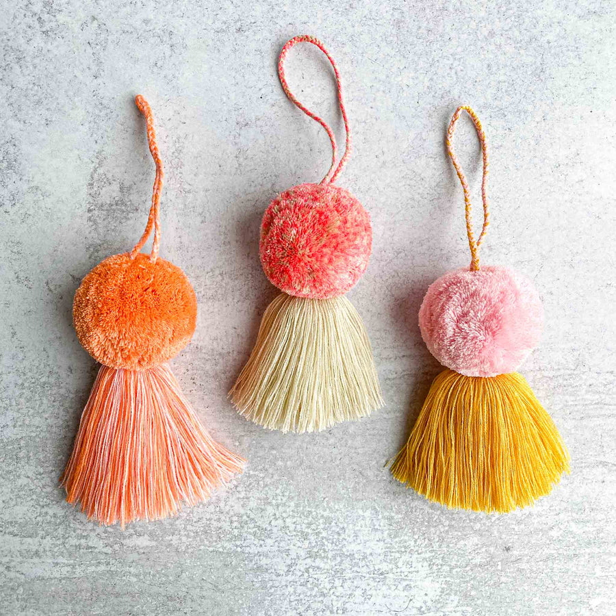 Aerial view of three handmade Large Pom-Tassel from left to right tassel in orange, tassel in Pink, tassel in pink