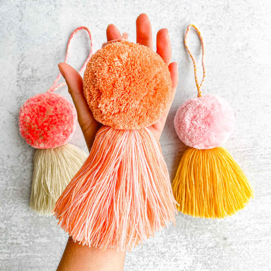 aerial view with a close up shot holding the fluffy pom pom in orange showing size