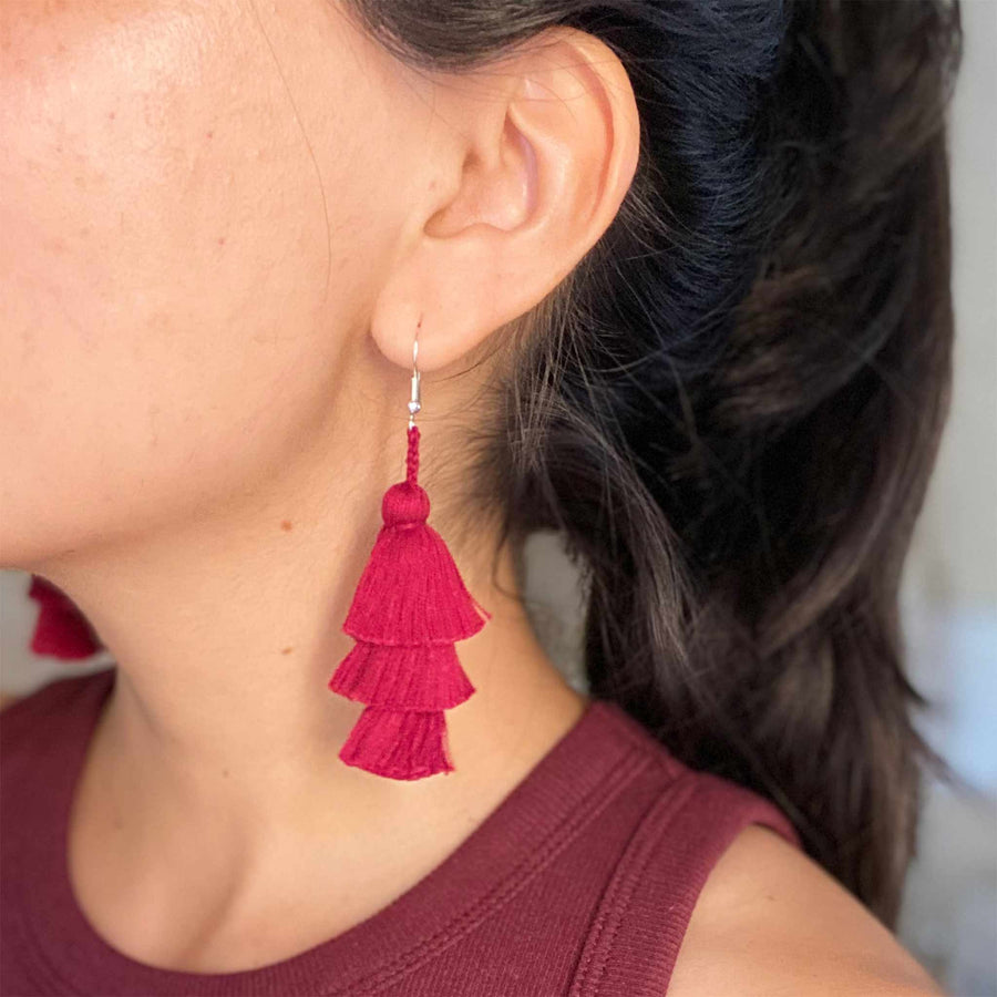 Burgundy Tassel Earrings worn by a woman