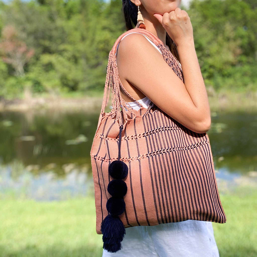 Lifestyle image of women carrying over her shoulder the Handwoven-Loom-Tote-Bag-in-Mauve-in-Navy-Stripes