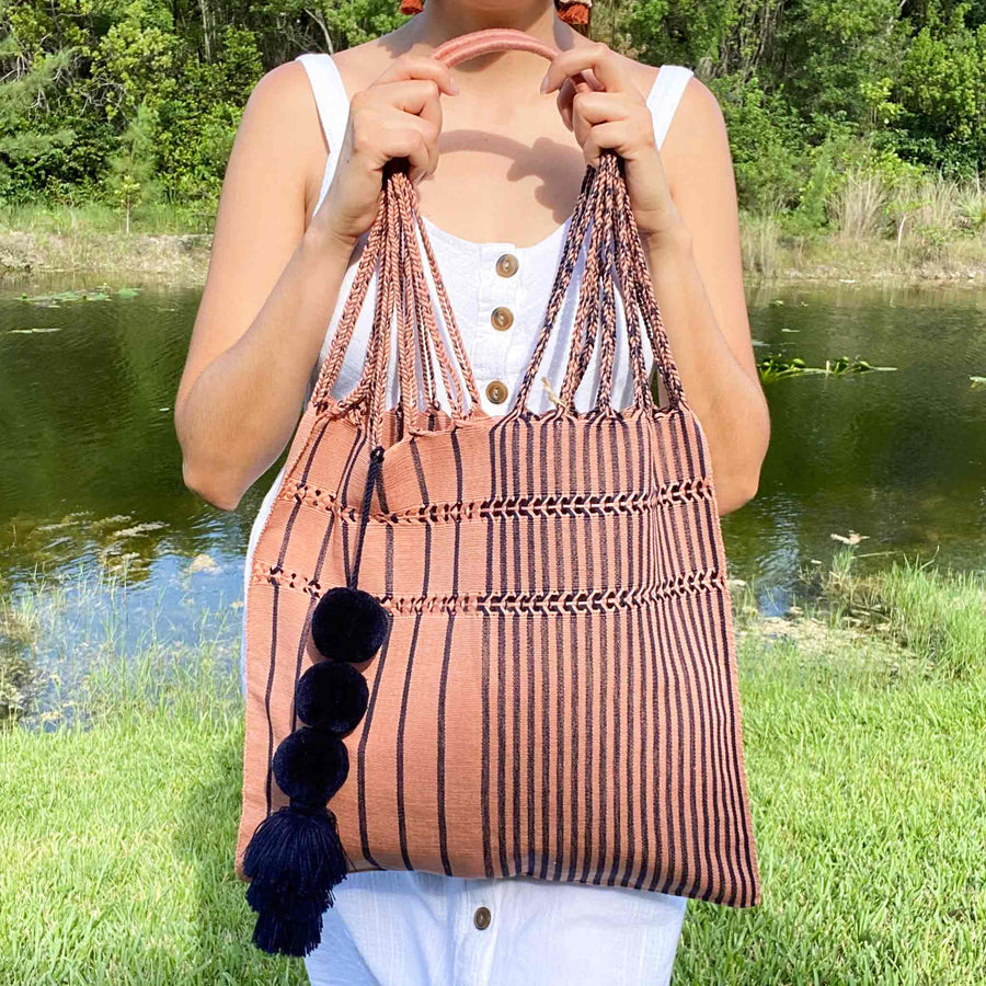 Woman carrying over her shoulder the Handwoven-Loom-Summer-Tote-Bag-in-Mauve-in-Navy-Stripes
