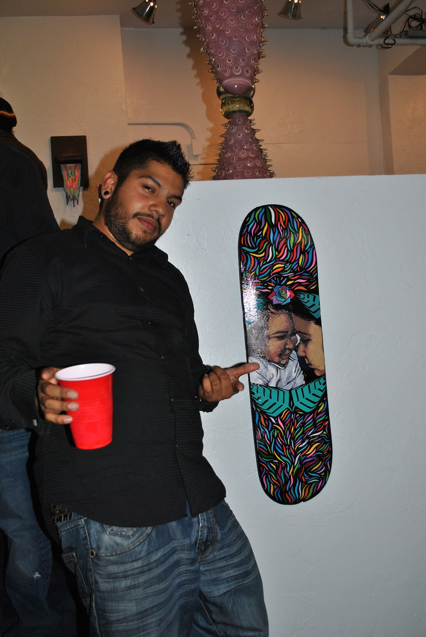 Artist standing in front of his artwork holding a cup