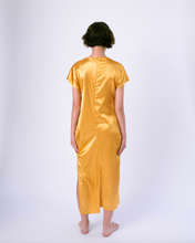 Load image into Gallery viewer, back of gold colored satin maxi tshirt dress with side slit on woman