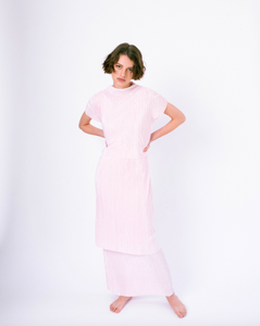 Front of pink pleated tiered maxi dress with mock neck and short sleeves on woman