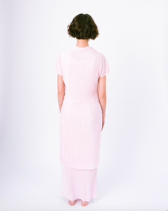 Back of pink pleated tiered maxi dress with mock neck and short sleeves on woman