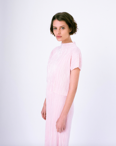 Side profile of pink pleated tiered maxi dress with mock neck and short sleeves on woman