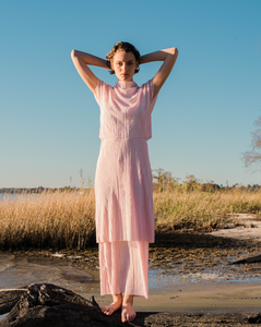 pink pleated tiered maxi dress with mock neck and short sleeves on woman on beach