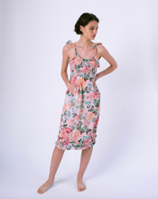 Load image into Gallery viewer, Front of pink floral midi dress with pockets & smocked top . Ruffles on straps and skirt.