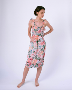 Front of pink floral midi dress with pockets & smocked top . Ruffles on straps and skirt.