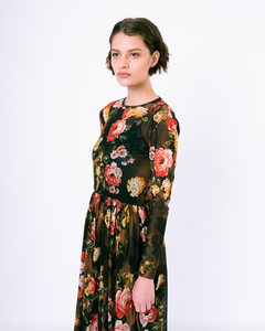 Side profile of floral print brown mesh overlay a-line dress with long sleeves over attached satin slip on woman