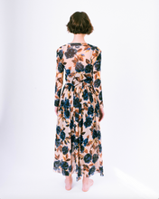 Load image into Gallery viewer, Back view of blue floral print on tan mesh overlay a-line dress with long sleeves over slip dress on woman