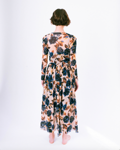 Back view of blue floral print on tan mesh overlay a-line dress with long sleeves over slip dress on woman