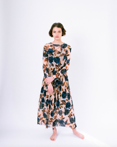 Front view of blue floral print on tan mesh overlay a-line dress with long sleeves over slip dress on woman